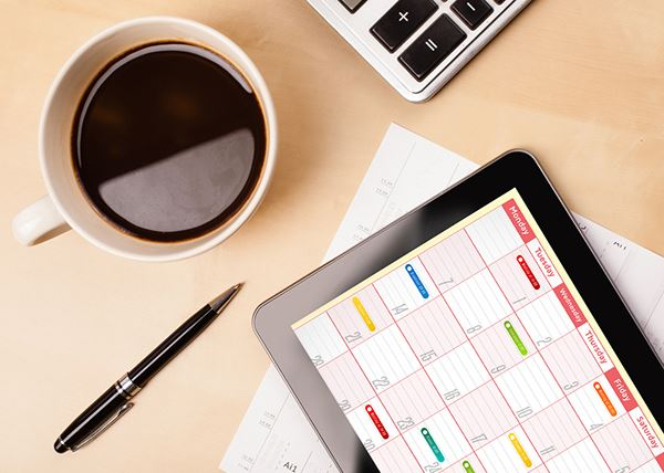 A scheduling tablet with a calendar displayed sits next to a cup of coffee.