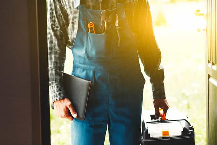Plumber standing at door holding his tool box